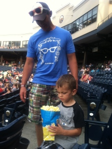 A little boy and a VERY large container of popcorn.